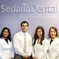 Dentists posing below Sedalia Dental sign