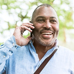 Smiling man on cellphone outdoors
