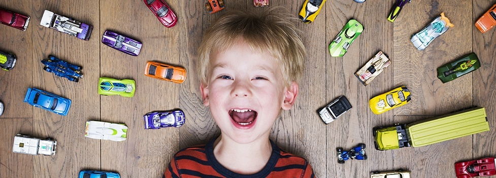 Smiling young boy surrounded by toy cars