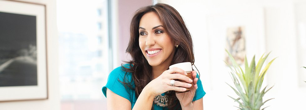 Woman with beautiful smile holding cup of coffee